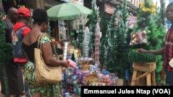 Marché central de Yaoundé, une femme négocie le prix du sapin, à Yaoundé, le 13 décembre 2018. (VOA/Emmanuel Jules Ntap)