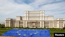 FILE - A large European Union flag is displayed in front of Romania's parliament building in Bucharest, May 9, 2013.