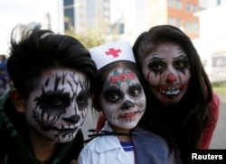 FILE - People in costume pose for a photograph during Halloween celebrations in La Paz, Bolivia, October 31, 2018. (REUTERS/David Mercado)