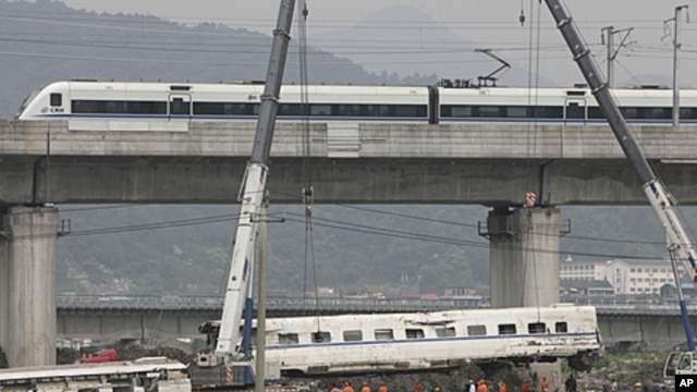 A high speed bullet train runs past a railway bridge as workers use cranes to lift a wrecked carriage onto a truck after two trains crashed and derailed in Wenzhou, Zhejiang province, July 26, 2011.
