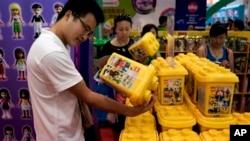 2013年7月25日,在北京玩博会上,中国游客查看参展的塑料积木。最新数据显示,中国经济出现好转迹象,但内需仍有待加强。