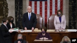 Vice President Mike Pence and Speaker of the House Nancy Pelosi, D-Calif., read the final certification of Electoral College votes cast in November's presidential election during a joint session of Congress. (AP Photo/J. Scott Applewhite, Pool)