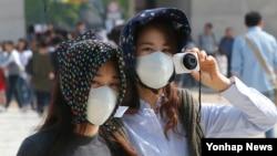 한반도 전역에 황사가 나타난 25일 서울 종로구 경복궁을 찾은 관광객들이 마스크를 쓰고 있다.