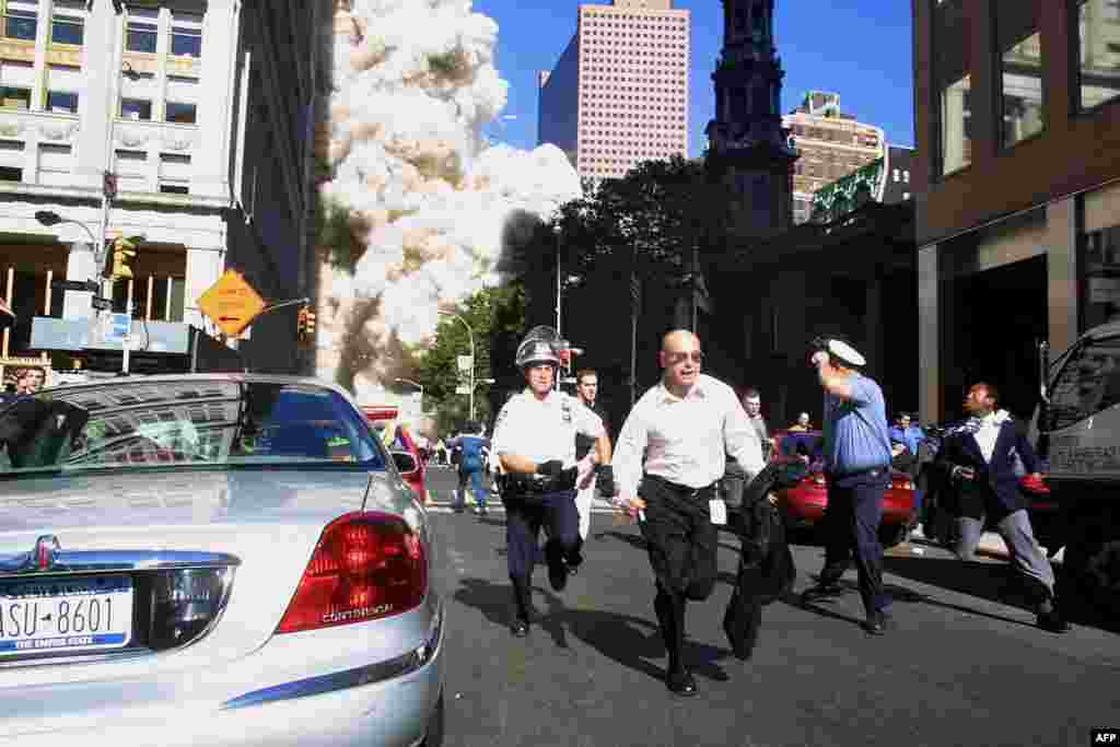 (FILE)Police and pedestrians run for cover during the first collapse of the World Trade Center Tower after the landmark skyscrapers were struck by two hijacked airplanes 11 September 2001 in New York . AFP PHOTO/Doug KANTER (Photo by DOUG KANTER / AFP)