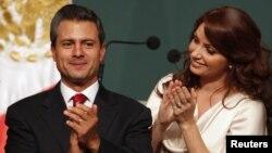 Enrique Pena Nietto (kiri) kandidat dari Partai Lembaga Revolusional (PRI), didampingi istrinya Angelica Rivera, bertepuk tangan saat diumumkannya hasil awal Pilpres Meksiko (1/7).