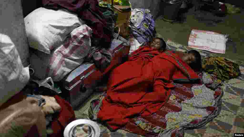Boys sleep on the floor of a wedding hall after leaving their house to take shelter from the impact of the approaching Cyclone Phailin, in the eastern Indian state of Odisha.