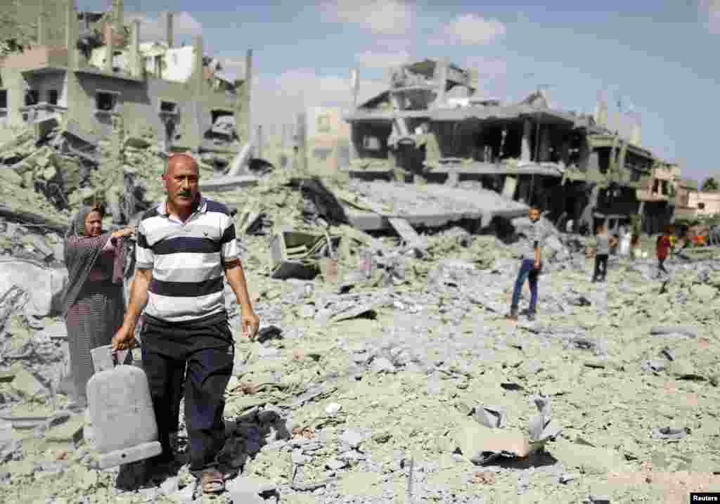 A Palestinian man carries a gas canister that he salvaged from his destroyed house in Beit Hanoun town, which witnesses said was heavily hit by Israeli shelling and air strikes during the Israeli offensive, in the northern Gaza Strip, July 26, 2014.