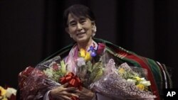 Aung San Suu Kyi tersenyum seusai menerima karangan bunga dan selendang tradisional Chin sebelum berpidato di Fort Wayne, Indiana, salah satu wilayah dengan komunitas Burma tebesar di AS (25/9).