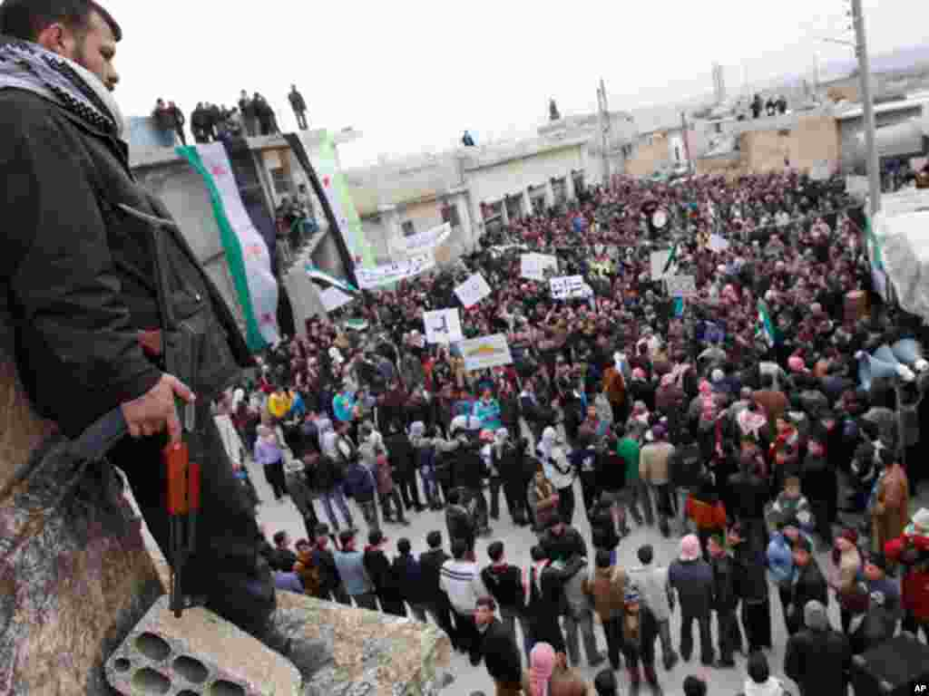 A member of the Free Syrian Army stands guard as anti-Syrian regime protesters hold a demonstration in Idlib, Syria, on February 6, 2012. (AP)