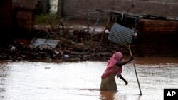 FILE - A Sudanese woman makes her way through flood water in Khartoum, Sudan, Aug. 6, 2013.