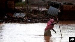 홍수로 침수된 수단 수도 하르툼 거리를 건너는 여성