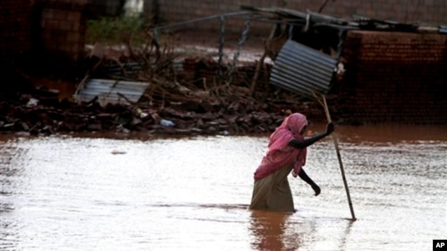 A Sudanese woman makes her way through flood water in Khartoum, Sudan, Aug. 6, 2013.