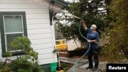 Vicki Nightingale sprays water on her home in Glen Ellen, California, Oct. 11, 2017.