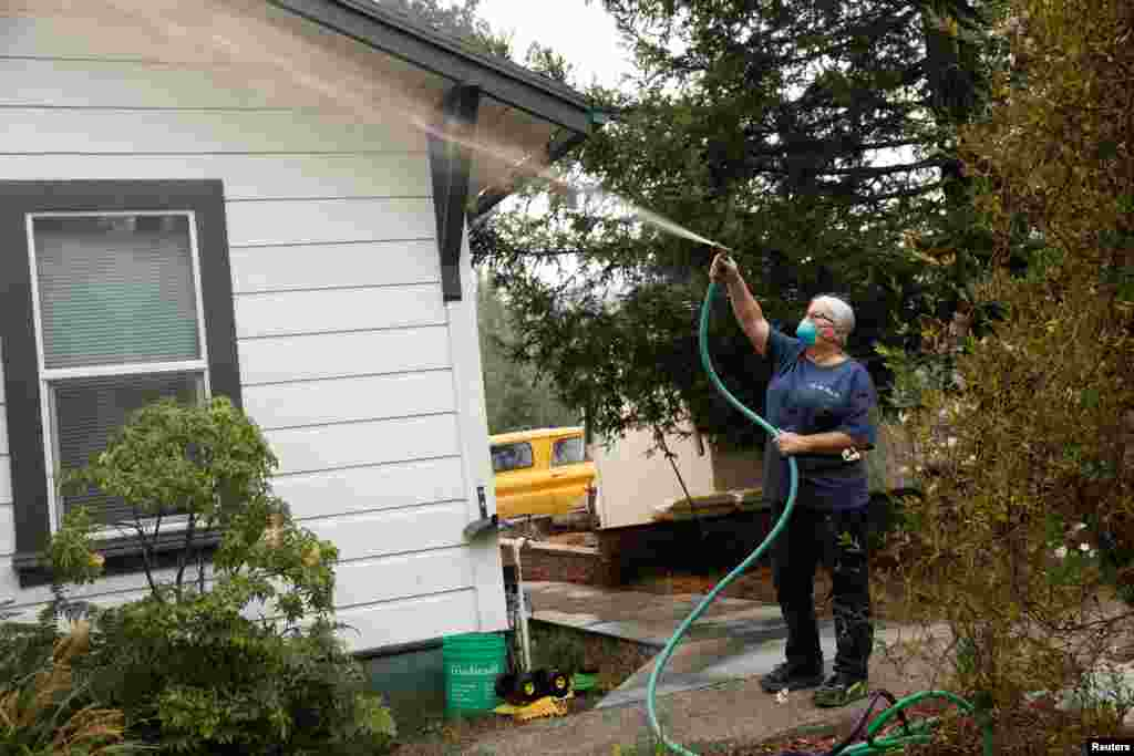Vicki Nightingale sprays water on her home in Glen Ellen, California, Oct. 11, 2017.
