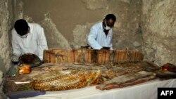 Des archéologues égyptiens examinent un sarcophage en bois découvert dans une tombe de l'ère pharaonique à Draa Abul Naga, près de Louxor, Egypte, le 18 avril 2017.