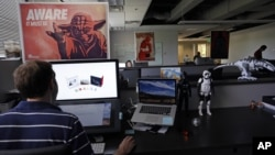 "An employee at Sphero, a fast-growing toy robotics company, works surrounded by ""Star Wars"" toys and posters, at the company headquarters in Boulder, Colorado, July 24, 2015."
