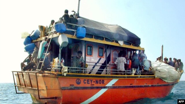 FILE - Sri Lankan asylum seekers stay on their traditional boat near Dili's port.