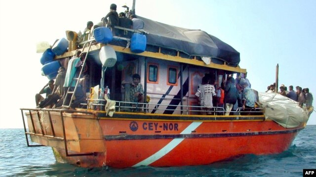 Sri Lankans asylum seekers stay on their traditional boat near Dili's port, July 31, 2002.