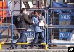 Ảnh tư liệu - Cảnh sát Thổ Nhĩ Kỳ hộ tống một di dân sau khi chuyến tàu đầu tiên đưa những người di cư từ đảo Lesbos, Ai Cập, cập bến ở cảng Dikili, Thổ Nhĩ Kỳ, đưa vào thực hiện một kế hoạch của EU nhằm ngăn chặn người di cư vào châu Âu, ngày 4 tháng 4 năm 2016.
