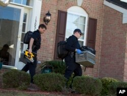 FILE - Prince William County, Va., officers collect evidence at a house in Woodbridge, Va., Feb. 29, 2016, following a fatal shooting at the residence during a domestic dispute.