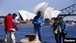 Chinese tourists stand on rocks on the edge of Sydney Harbour as they take pictures of themselves in front of the Sydney Opera House in Sydney, Australia.