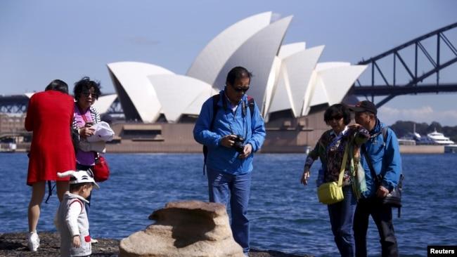 中国游客在澳大利亚悉尼港口以悉尼歌剧院为背景拍照留念。(2015年9月28日)