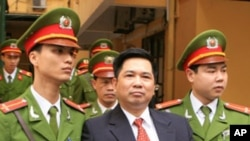 ທ່ານ Cu Huy Ha Vu ຖືກຕໍາຫລວດນໍາໄປສານເພື່ອດໍາເນີນຄະດີ ໃນສານໃນກຸງຮາໂນຍ ວັນທີ 4 ເມສາ 2011.