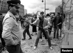 1990年6月2日档案照片: 东德边防士兵看着一名男子用钢钎捣毁柏林墙
