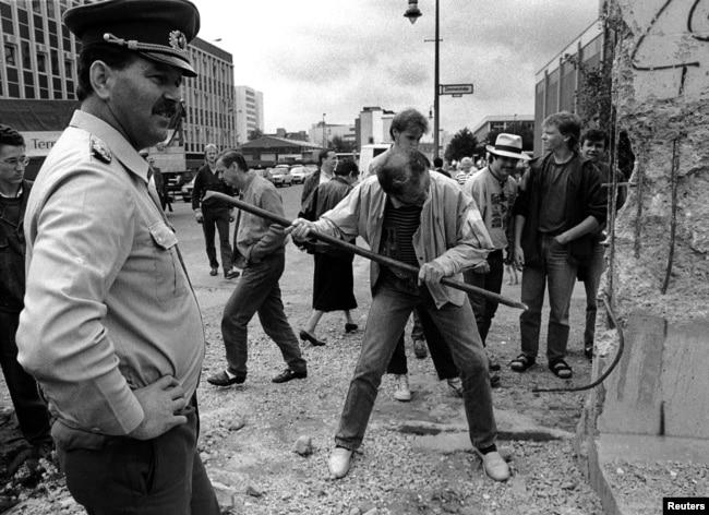 1990年6月2日档案照片: 东德边防士兵看着一名男子用锤子捣毁柏林墙