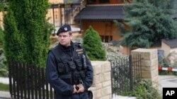 Seorang polisi berdiri di lokasi kejadian pembunuhan empat anggota keluarga di Brno, Republik Ceko (23/5). Tersanga pembunuhnya seorang warga AS telah ditangkap.