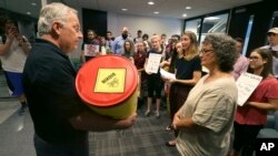 David Gray, left, director of external affairs at the Environmental Protection Agency Region VI office, accepts a barrel of letter from members of the Texas Campaign for the Environment at the EPA office in Dallas, Oct. 12, 2017. The letters to the EPA are calling for saving federal cleanup programs under the Trump Administration. The EPA has approved a plan to remove sediments laced with highly toxic dioxin from a partially submerged Superfund site near Houston damaged during Hurricane Harvey.