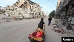 Palestinski dječak sa svojim bratom bježi iz kuće u Gazi nakon napada izraelske vojske