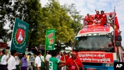 Supporters of Myanmar's opposition leader Aung San Suu Kyi's National League for Democracy party, on the party's campaign truck, right, pass an office of the rival Union Solidarity and Development Party in Meiktila, Mandalay Region, Myanmar, Nov. 4.