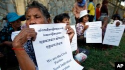 FILE - Victims of the Khmer Rouge regime hold a protest to demand individual reparations in front of an entrance to the U.N.-backed war crimes tribunal as a hearing is held in Phnom Penh, Cambodia, Oct. 17, 2014.