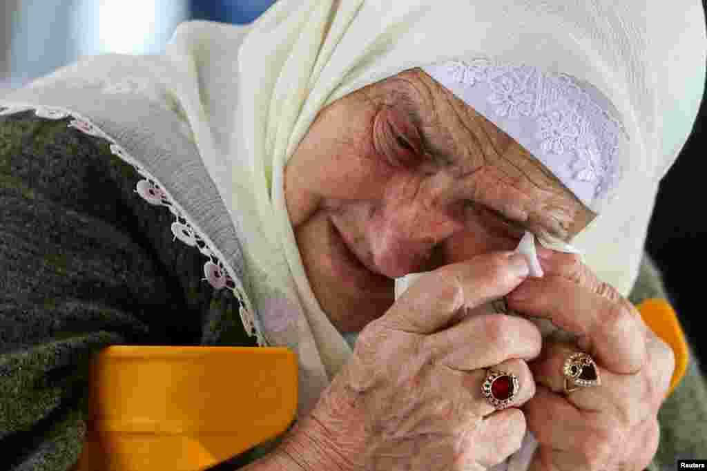 A Bosnian Muslim woman reacts as she awaits the final verdict of former Bosnian Serb military leader Ratko Mladic in the Srebrenica-Potocari Genocide Memorial Center, Bosnia and Herzegovina.