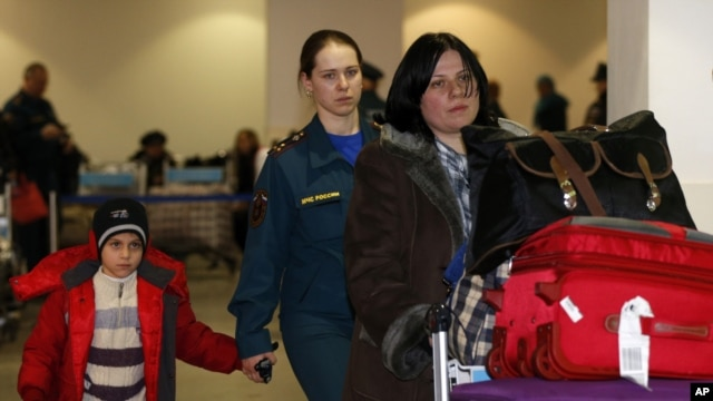 A Russian woman and her daughter, left, are escorted by a Russian emergency situation officer leave passport control zone just after arrivingl from Beirut in Moscow Domodedovo airport, January 23, 2013.