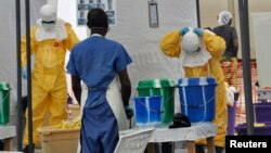 FILE - A Doctors Without Borders health worker takes off his protective gear under the surveillance of a colleague at a treatment facility for Ebola victims in Monrovia, Sept. 29, 2014.