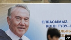 A man walks past an election poster of Kazakh President Nursultan Nazarbayev in Almaty, Feb. 22, 2011.