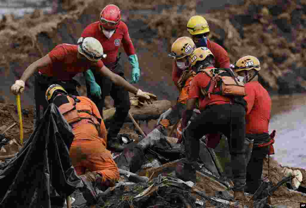Firefighters pull a body from the mud days after a dam collapse in Brumadinho, Brazil. Firefighters carefully moved over treacherous mud, sometimes walking, sometimes crawling, in search of survivors or bodies four days after a dam collapse that buried mine buildings and surrounding neighborhoods with iron ore waste.
