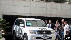 """Šef tima inspektora UN, profesor Ake Selstrom i Andjela Kejn, predstavnica UN za pitanja razoružanja posmatraju kako tim inspektora napušta hotel """"Four Seasons"""" u Damasku."""