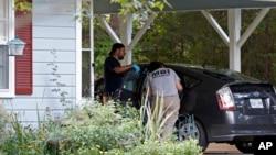Dos investigadores inspeccionan un auto en la cochera de la casa de las monjas asesinadas.