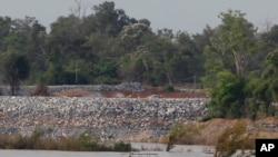 FILE - A fishing boat passes near a construction site of the Don Sahong dam, near the Cambodia-Laos border, June 20, 2016.