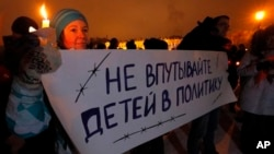 "FILE - Russian child's death follows international controversy over the Russian ban on U.S. adoptions; protest sign says ""Do not involve children in politics,"" St. Petersburg, Dec. 26, 2012."