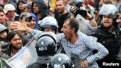 一个试图移民的男子在被斯洛文尼亚警察包围时的反应。