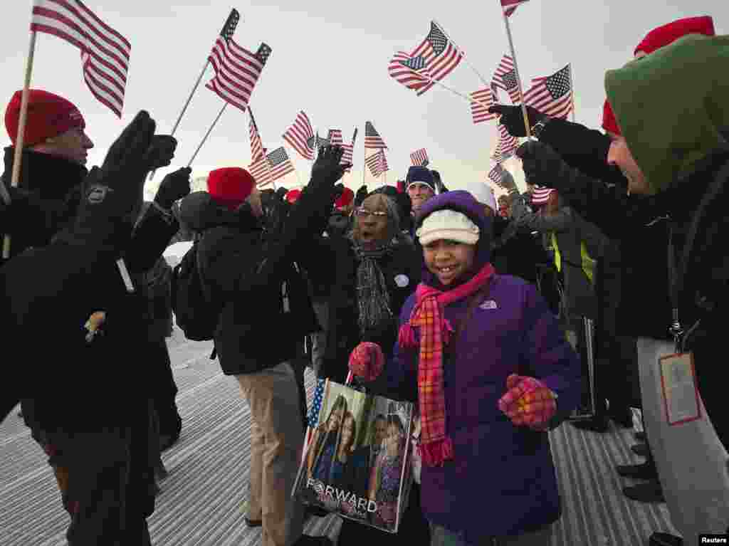 People cheer as the enter the National Mall before the ceremonial swearing-in ceremonies on the West front of the U.S. Capitol in Washington January 21, 2013