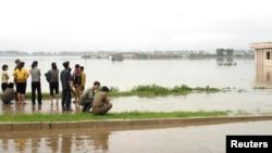 지난해 7월 홍수 피해를 입은 북한 안주시 마을 주민들이 침수된 주택 밖으로 대피했다. (자료사진)