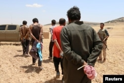 FILE - Men, who the Democratic Forces of Syria fighters claimed were Islamic State fighters, walk as they are taken prisoners after SDF advanced in the southern rural area of Manbij, in Aleppo Governorate, Syria, May 31, 2016.