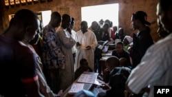 Les électeurs font la queue pour retirer leur carte au bureau de vote à l'école Koudoukou dans le quartier PK5, à Bangui, 14 décembre 2015