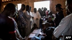 FILE - Voters on a constitutional referendum line up to collect their cards at a polling station in Bangui, Central African Republic, Dec. 2015. Elections for president and parliament are scheduled for Wednesday.
