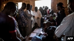Voters queue to collect their cards at the polling station at the Koudoukou school in the flashpoint PK5 district in Bangui, Central African Republic, Dec.14, 2015.